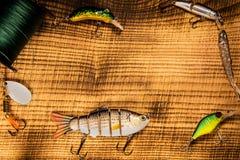 Αλιευτικό εργαλείο, τεχνητό δόλωμα σε ένα αρπακτικό ζώο σε ένα ξύλινο υπόβαθρο, τοπ wobblers άποψης και διάφορες σκοινιά και λαβί Στοκ Εικόνες