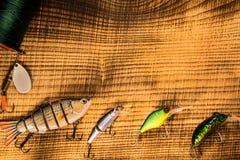 Αλιευτικό εργαλείο, τεχνητό δόλωμα σε ένα αρπακτικό ζώο σε ένα ξύλινο υπόβαθρο, τοπ wobblers άποψης και διάφορες σκοινιά και λαβί Στοκ Εικόνα