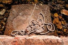 Αλιεύοντας το σχοινί που ζαρώνεται και που περιλαμβάνεται αριστερά στον ηλιόλουστο βράχο Στοκ Εικόνα
