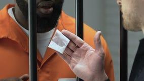 Αλλοιωμένος δεσμοφύλακας που δίνει τη συσκευασία κοκαΐνης στον αφροαμερικανό φυλακισμένο, εύνοια απόθεμα βίντεο