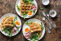 Αλμυρές βάφλες πατατών με το βρασμένα αυγό, το ζαμπόν και το arugula στο ξύλινο υπόβαθρο, τοπ άποψη Εξυπηρετούμενο πρόγευμα, πρόχ Στοκ φωτογραφία με δικαίωμα ελεύθερης χρήσης