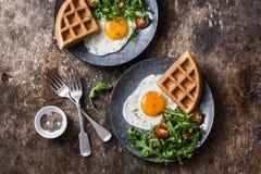 Αλμυρές βάφλες, τηγανισμένα αυγά και arugula, σαλάτα ντοματών κερασιών - εύγευστο υγιές πρόγευμα στο ξύλινο υπόβαθρο Στοκ Φωτογραφία