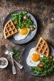 Αλμυρές βάφλες, τηγανισμένα αυγά και arugula, σαλάτα ντοματών κερασιών - εύγευστο υγιές πρόγευμα στο ξύλινο υπόβαθρο Στοκ εικόνα με δικαίωμα ελεύθερης χρήσης