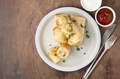 Αλμυρός crepe οι ρόλοι με την πλήρωση επίγειου κρέατος που εξυπηρετείται με την ξινή σάλτσα κρέμας και ντοματών στοκ φωτογραφία