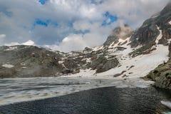 Αλπική λίμνη παγωμένη κατά το ήμισυ και κατά το ήμισυ αριθ. Στοκ Εικόνες