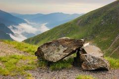 Αλπικό τοπίο με τους μικρούς βράχους και υπόβαθρο με τα βουνά Fagaras παράλληλα με το διάσημο δρόμο Transfagarasan στοκ φωτογραφία