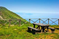 Αλπικό τοπίο με τους ξύλινους πάγκους και τον πίνακα και η Μεσόγειος στο υπόβαθρο σε Beigua εθνικό Geopark στοκ φωτογραφίες με δικαίωμα ελεύθερης χρήσης