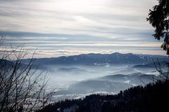 Αλπικό χειμερινό πανόραμα με έναν misty ουρανό κοιλάδων και ομιχλώδη χειμώνα βουνών στα ευρωπαϊκά όρη στοκ εικόνες με δικαίωμα ελεύθερης χρήσης