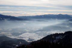 Αλπικό χειμερινό πανόραμα με έναν misty ουρανό κοιλάδων και ομιχλώδη χειμώνα βουνών στα ευρωπαϊκά όρη στοκ φωτογραφία με δικαίωμα ελεύθερης χρήσης