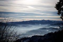 Αλπικό χειμερινό πανόραμα με έναν misty ουρανό κοιλάδων και ομιχλώδη χειμώνα βουνών στα ευρωπαϊκά όρη στοκ φωτογραφίες