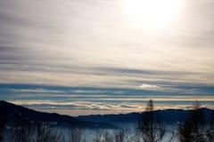 Αλπικό χειμερινό πανόραμα με μια misty κοιλάδα με τον ομιχλώδη χειμερινό ουρανό σύννεφων και βουνών στα ευρωπαϊκά όρη στοκ φωτογραφίες