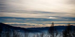 Αλπικό χειμερινό πανόραμα με μια misty κοιλάδα με τον ομιχλώδη χειμερινό ουρανό σύννεφων και βουνών στα ευρωπαϊκά όρη στοκ εικόνα με δικαίωμα ελεύθερης χρήσης