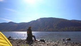 αλσατικό Δύο βίντεο στο ένα Η στρατοπεδεύοντας γυναίκα κάθεται στην τράπεζα της λίμνης βουνών Κλείστε επάνω των ποδιών κοριτσιών  απόθεμα βίντεο