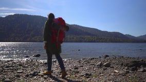 αλσατικό Δύο βίντεο στο ένα Η στρατοπεδεύοντας γυναίκα κάθεται στην τράπεζα της λίμνης βουνών Κλείστε επάνω των ποδιών κοριτσιών  φιλμ μικρού μήκους