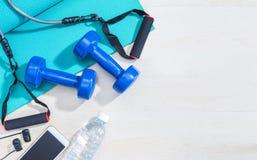 Αλτήρες, εξοπλισμός άσκησης, χαλί γιόγκας γυμναστικής, κινητό τηλέφωνο, earphon στοκ φωτογραφία