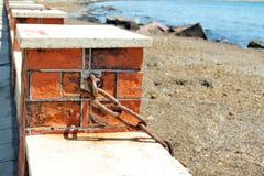 Αλυσίδα στο φράκτη τούβλου κοντά στον ωκεανό στοκ φωτογραφίες με δικαίωμα ελεύθερης χρήσης