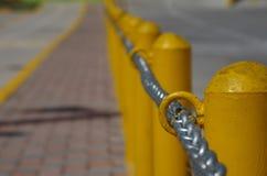 Αλυσίδα σύμφωνα με μια κίτρινη μετα γραμμή σε μια οδό Στοκ Εικόνες