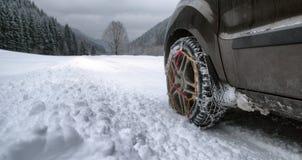 Αλυσίδες χιονιού στη ρόδα στο χειμερινό δρόμο στοκ εικόνα