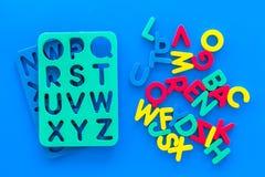 Αλφάβητο για την έννοια παιδιών Αγγλικές επιστολές στην αναταραχή κοντά στο διάτρητο στην μπλε τοπ άποψη υποβάθρου στοκ φωτογραφίες