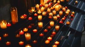 Αμέτρητα κεριά, αναμμένα στο εσωτερικό μιας πολύ σκοτεινής καθολικής εκκλησίας απόθεμα βίντεο