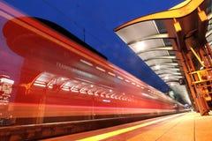 Αμαξοστοιχία περιφερειακού σιδηροδρόμου που αφήνει έναν σταθμό Στοκ Εικόνες