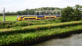 Αμαξοστοιχία περιφερειακού σιδηροδρόμου που κινείται μέσω της επαρχίας κατά μήκος του καλλιεργήσιμου εδάφους και της τράπεζας τη  Στοκ φωτογραφίες με δικαίωμα ελεύθερης χρήσης