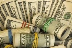Αμερικανικά δολάρια στους ρόλους από εκατό τραπεζογραμμάτια Μέρος των δολαρίων στοκ εικόνα