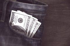 Αμερικανικά δολάρια τραπεζογραμματίων στην τσέπη τζιν Στοκ Φωτογραφία