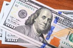 Αμερικανικά τραπεζογραμμάτια δολαρίων στον ξύλινο πίνακα Στοκ Φωτογραφία