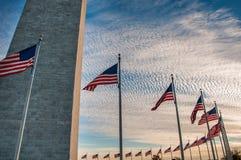 Αμερικανικές σημαίες που περιβάλλουν το μνημείο της Ουάσιγκτον στο ηλιοβασίλεμα Στοκ Φωτογραφία