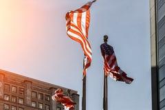 Αμερικανική εθνική σημαία ενάντια στον ψηλό ουρανοξύστη, ΗΠΑ μια ηλιόλουστη ημέρα Στοκ εικόνα με δικαίωμα ελεύθερης χρήσης