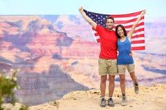 Αμερικανική σημαία εκμετάλλευσης ζευγών τουριστών ΑΜΕΡΙΚΑΝΙΚΟΥ ταξιδιού Στοκ εικόνες με δικαίωμα ελεύθερης χρήσης