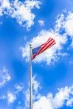 Αμερικανική σημαία ενάντια σε έναν μπλε ουρανό με τα άσπρα σύννεφα Στοκ Φωτογραφίες