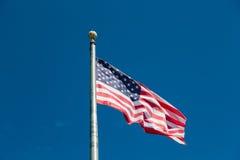 Αμερικανική σημαία που πετά από το ασημένιο κοντάρι σημαίας στο μπλε ουρανό στοκ φωτογραφία με δικαίωμα ελεύθερης χρήσης
