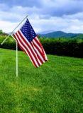 Αμερικανική σημαία που πετά στον αέρα με τα βουνά στο υπόβαθρο Στοκ εικόνες με δικαίωμα ελεύθερης χρήσης