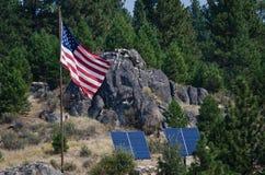 Αμερικανική σημαία που στέκεται στην αγριότητα εκτός από δύο ηλιακά πλαίσια στοκ εικόνες με δικαίωμα ελεύθερης χρήσης