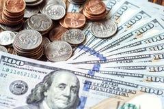 Αμερικανικοί λογαριασμοί εκατό δολαρίων χρημάτων με το σωρό νομισμάτων σωρός χρημάτων χεριών έννοιας νομισμάτων που προστατεύει τ Στοκ Φωτογραφίες