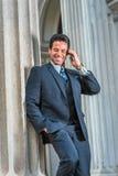 Αμερικανικός επιχειρηματίας Μεσαίωνα που μιλά στο τηλέφωνο κυττάρων έξω από Στοκ Φωτογραφία