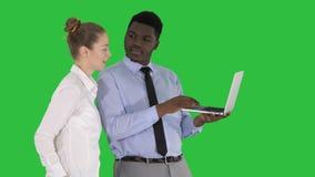 Αμερικανικός επιχειρησιακός σύμβουλος Afro που παρουσιάζει κάτι στην οθόνη lap-top που μιλά στη λευκιά επιχειρηματία σε μια πράσι απόθεμα βίντεο