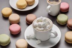 Αμερικανικός καφές, cappuccino με marshmallow, πολύχρωμα macaroons στο γκρίζο υπόβαθρο Στοκ Φωτογραφίες