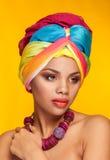 Αμερικανικό κορίτσι Afro που φορά ένα εθνικό τουρμπάνι στο κίτρινο υπόβαθρο Στοκ Φωτογραφία