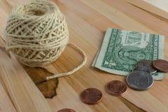 Αμερικανικό νόμισμα και μια σφαίρα της σειράς στον ξύλινο πίνακα στοκ φωτογραφία
