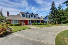 Αμερικανικό σπίτι εξωτερικό με την μπλε και άσπρη περιποίηση Επίσης κόκκινη μπροστινή πόρτα στοκ εικόνα με δικαίωμα ελεύθερης χρήσης