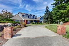 Αμερικανικό σπίτι εξωτερικό με την μπλε και άσπρη περιποίηση Επίσης κόκκινη μπροστινή πόρτα στοκ φωτογραφία με δικαίωμα ελεύθερης χρήσης