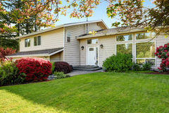 Αμερικανικό σπίτι με τον καλά κρατημένους χορτοτάπητα και τα λουλούδια Στοκ Φωτογραφίες