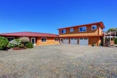 Αμερικανικό σπίτι προκυμαιών, πορτοκαλί εξωτερικό χρώμα και τρία διαστήματα γκαράζ Στοκ Φωτογραφία