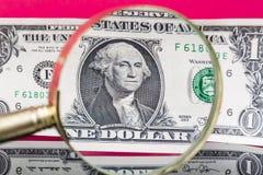 Αμερικανικό τραπεζογραμμάτιο δολαρίων μέσω μιας ενίσχυσης - γυαλί στο συμπαθητικό κόκκινο υπόβαθρο Στοκ φωτογραφία με δικαίωμα ελεύθερης χρήσης