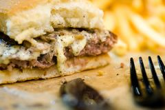 αμερικανικό χάμπουργκερ βόειου κρέατος με το τυρί και τηγανιτές πατάτες στο όμορφο bistro γρήγορου φαγητού και καφέδων εύγευστο χ στοκ εικόνα