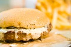 αμερικανικό χάμπουργκερ βόειου κρέατος με το τυρί και τηγανιτές πατάτες στο όμορφο bistro γρήγορου φαγητού και καφέδων εύγευστο χ στοκ εικόνες