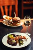 Αμερικανικό χάμπουργκερ με το ποτήρι της μπύρας ή κρασί στο εστιατόριο, της μπύρας, του χάμπουργκερ, του κρασιού και άλλων αμερικ στοκ φωτογραφία